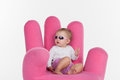 Fashion baby girl sitting at pink chair in form of hand looking away glasses isolated over white background Royalty Free Stock Images