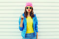 Fashion bad girl expression showing hand with middle finger sign in colorful clothes over white background wearing a pink hat Royalty Free Stock Photo