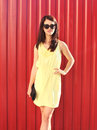 Fashion beautiful brunette woman wearing yellow dress and sunglasses with handbag clutch in city a Stock Photos