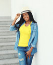 Fashion beautiful smiling african woman wearing straw hat and jeans clothes in city Royalty Free Stock Photo