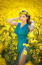 Fashion beautiful young woman in blue dress smiling in rapeseed field in bright sunny day and yellow flowers wreath posing outdoor Royalty Free Stock Photos