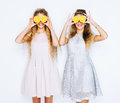 Fashion and beauty. Two stunning beauties girls having fun with slices of oranges closing by them eyes.