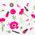 Fashion blogger desk with cosmetics - lipstick, eye shadows, nail polish and pink flowers on white background. Flat lay, top view. Royalty Free Stock Photo