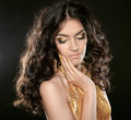 Fashion brunette girl with Long curly hair, beauty makeup, luxury jewelry. Beautiful attractive young woman in golden dress Royalty Free Stock Photo