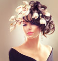 Fashion brunette girl with magnolia flowers hairstyle Royalty Free Stock Photo