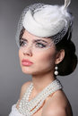Fashion Brunette Retro Model Portrait. Pearls Jewelry and Hairst