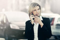 Fashion business woman calling on cell phone next to her car Royalty Free Stock Photo