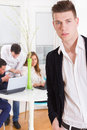 Fashion casual man in a business atmosphere with colleagues behi young modern men behind him Stock Image