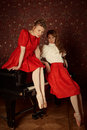 Fashion caucasian ballerinas sitting on the piano and laughing