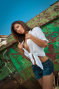 Fashion caucasian model posing outdoor in front of an old boat sexy brunette with white shirt and denim shorts near Stock Images