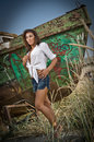 Fashion caucasian model posing outdoor in front of an old boat sexy brunette with white shirt and denim shorts near Royalty Free Stock Images