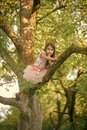 Kids enyoj happy day. Fashion child in fashionable dress hide on tree, secrecy Royalty Free Stock Photo