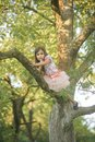 Fashion child in fashionable dress hide on tree, secrecy Royalty Free Stock Photo