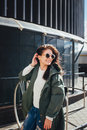 Fashion closeup portrait of nice pretty young hipster woman posing in sunglasses Outdoor .Brunette happy girl in green Royalty Free Stock Photo
