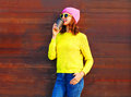 Fashion cool girl with coffee cup in colorful clothes over wooden background wearing pink hat yellow sweater Royalty Free Stock Photo