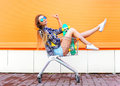 Fashion cool girl having fun in shopping trolley cart with skateboard Royalty Free Stock Photo