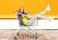 Fashion cool girl having fun sitting in shopping trolley cart Royalty Free Stock Photo
