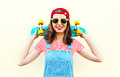 Fashion cool girl smiling with skateboard over white Royalty Free Stock Photo