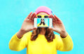 Fashion cool girl taking photo self portrait on smartphone over white background wearing colorful clothes and sunglasses