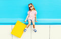 Fashion cool kid with shopping bag on colorful blue background Royalty Free Stock Photo