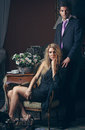 Fashion couple portrait of a in low key elegant blond lady seated Stock Photos