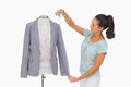 Fashion designer measuring blazer sleeve on mannequin white background Royalty Free Stock Images