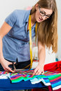 Fashion designer or tailor working in studio freelancer on a design draft and cutting fabrics with scissors Royalty Free Stock Photo