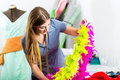 Fashion designer or tailor working in studio freelancer on a design draft with a feather boa Stock Image