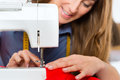 Fashion designer or tailor working in studio freelancer on a design draft she sews with a sewing machine Stock Photo