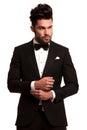 Fashion elegant man in tuxedo fixing his sleeve Royalty Free Stock Photo