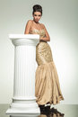 Fashion elegant woman in golden dress leaning on a column Royalty Free Stock Photo