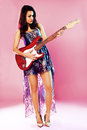 Fashion girl with guitar playing hard rock over a pink background Royalty Free Stock Images
