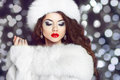 Fashion girl model posing in fur coat and white furry hat winte winter beautiful woman luxury clothes over boker christmas lights Stock Photography