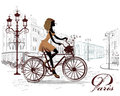 Fashion girl rides a bicycle decorated with a musical stave and butterflies the streets of the old town Stock Photos