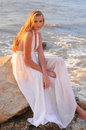 Fashion girl in a white dress beautiful sitting on rock the sea Stock Photography