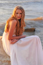 Fashion girl in a white dress beautiful sitting on rock the sea Stock Photos