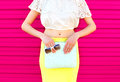 Fashion glamour woman with handbag clutch and sunglasses over colorful pink Royalty Free Stock Photo