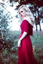 Fashion gorgeous young blonde woman in beautiful red dress in a fairy-tale forest. magic atmosphere. Retouched toning shot Royalty Free Stock Photo