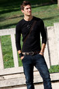 Fashion guy cool model outdoor a nice italian trendy posing black t shirt and jeans beautiful face and eyes concept Stock Images