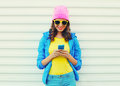 Fashion happy cool smiling girl using smartphone in colorful clothes over white background wearing pink hat yellow sunglasses Royalty Free Stock Photo