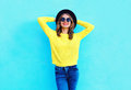 stock image of  Fashion happy pretty smiling woman wearing a black hat and yellow knitted sweater over colorful blue