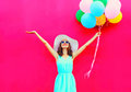 Fashion happy smiling woman with an air colorful balloons is having fun in summer over a pink background