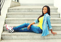 Fashion happy smiling young african woman wearing jeans clothes sitting resting on stairs Royalty Free Stock Photo