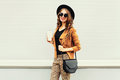 Fashion happy young smiling woman with coffee cup wearing a retro elegant hat, sunglasses, brown jacket and black handbag Royalty Free Stock Photo