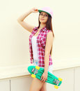 Fashion hipster cool girl in colorful pink clothes with skate Royalty Free Stock Photo