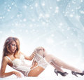 Fashion image of young and sexy redhead woman in white lingerie over a winter background with a snow Stock Image