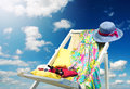 Fashion leisure hat and dress on deckchair against blue sky Stock Photography