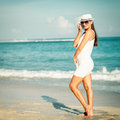 Fashion lifestyle beautiful girl on the beach at the day time in sunglasses and white hat travel and vacation Stock Photos