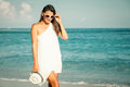 Fashion lifestyle beautiful girl on the beach at the day time in sunglasses and white hat travel and vacation Royalty Free Stock Images