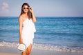 Fashion lifestyle beautiful girl on the beach at the day time in sunglasses and white hat travel and vacation Stock Photography